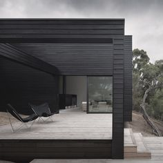This rural residence outside Melbourne by architects Studio Four features a blackened timber exterior and terraces that step down a hill