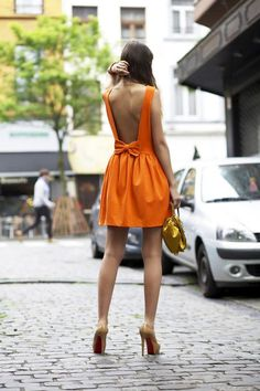 Wheretoget - Orange backless bow dress paired with nude pumps and a gold clutch bag