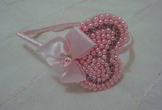 Tiara revestida em cetim rosa com lindo coração em miçanga rosa, strass e laço com botão em flor. Um acessório bonito e que faz toda a diferença da moda infantil. R$ 14,90
