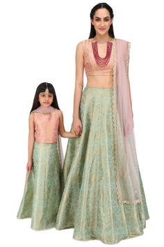 This Mother & Daughter set features a dusky rose sleeveless blouse in brocade. It comes along with mint lehenga in brocade and dusky rose dupatta in net with crochet lace. FIT: Fitted at bust and waist. CARE: Dryclean only. Mom Daughter Matching Dresses, Mom And Baby Dresses, Mom Dress, Mothers Dresses, Brocade Lehenga, Anarkali, Lehenga Choli, Sarees, Mother Daughter Fashion