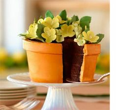photo of a creative birthday cake decorating idea - a cake in the shape of a flower pot with yellow flowers on top