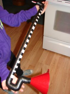 homemade saxaphone for science class made out of pvc pipe, electrical tape, a funnel, and a straw for a reed