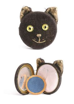 A very rare Schuco Cat's face compact - 1920s - large circular green and black glass eyes, pink felt nose, velvet ears, complete with powder and puff, slight wear to ears and fading