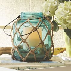 A few nautical-inspired accents can help set the coastal mood. Set large sea glass-inspired jar candles on side tables or hang jars from gazebo hooks or archways then fill them with LED candles, and a few seashells and sand, to help light the way once the sun sets.