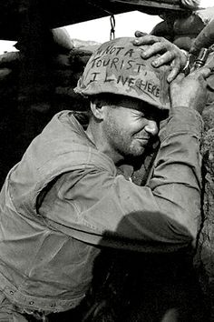 Clutching helmet and weapon, a Marine winces as North Vietnamese mortar rounds fly overhead during enemy shelling, Khe Sanh, South Vietnam (Image by Paul Stephanus)