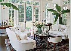 White couches, persian rug, a few plants.. so simple. And perfect. Of course the architecture helps..