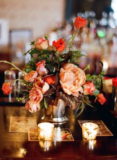 peach peonies with coral roses and ranunculus and foliage in a silver julep cup w/mercury glass votives