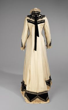 Ivory wool tea gown with black silk velvet and black lace decoration (back), American, 1875. Worn by Amelia Beard Hollenback (1844-1918), wife of the prominent financier and philanthropist John Welles Hollenback (1835-1927), in the months immediately after the Hollenback's first daughter was born, this early example illustrates Amelia Hollenback's keen awareness of fashion.