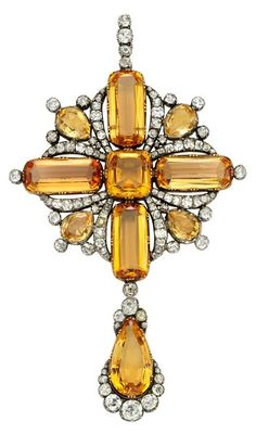 A Georgian imperial topaz and diamond pendant brooch, of cruciform design suspending a pear-shaped drop, mounted in silver and gold. Weight of Topaz = 75 cts, Total weight of diamonds = 8 ct. Via 1stdibs.