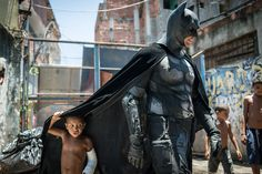 Description of . Children play around a man disguised as Batman at the Favela do Metro slum, area just near the Maracana stadium, in Rio de Janeiro, Brazil, on January 9, 2014. Families living in this shantytown within a stone's throw of Rio's mythical Maracana stadium refuse to have their homes demolished as part of a project to renovate the district before the FIFA World Cup circus pitches camp in June.  AFP PHOTO / YASUYOSHI CHIBA/AFP/Getty Images