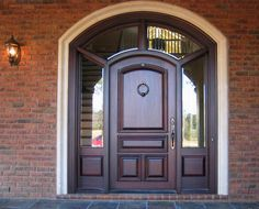 """Door Style DbyD-1079.  This impressive front entry has a 42"""" X 84"""" Style """"E-B-S"""" Solid Mahogany Door with standard raised molding with a keystone, rosettes, ledge and dentil on the outside and standard raised molding on the inside.  This segment top Entry has 20"""" wrap around sidelites with tempered beveled glass.  The stain color is Light Ebony and the door has Rocky Mountain Hardware."""