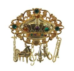 "This brooch pin with charms is made of gold alloy metal. Decorated with purple, green & gold crystals Size 3"" long X 2.4"" wide Made in the USA"