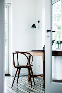 wood chair white walls black lamp