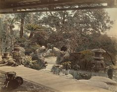 Garden view from the open porch of a Japanese tearoom. [possibly Nagasaki environment, 1863-1873]. [Photo, hand coloured albumine print, from series of 42 prints at Spaarnestad Photo, by Felice Beato, Kusakabe Kimbei or Raimund baron von Stillfried.]