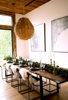 Jenni Kayne Holiday Party // Tablescape with hemlock, spruce, and Carolina cedar garland and tall taper candles and chairs with individual sheepskins.