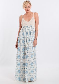 Cream-colored gauzy maxi dress featuring an empire waist with crochet overlay at the bust and a blue global-inspired medallion pattern at the skirt.