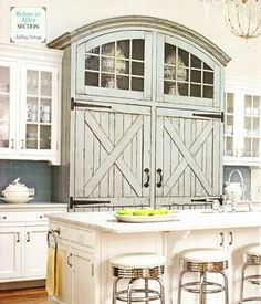 This refrigerator is disguised with distressed barn-style doors with strap hinges, arched top with heavy, but simple, trim with divided glass mullions.