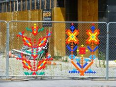 Multi-coloured cups are pushed into negative space to create chain link 8 bit fence designs.  Christchurch.