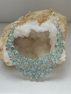 Hand-faceted pear-shaped and round brilliant Swiss Blue Topaz gemstones accentuate this elegant necklace, set in 925 sterling and sterling overlay.