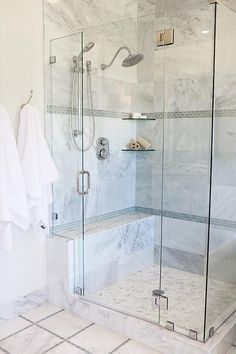 Lovely bathroom features a corner seamless glass shower clad in gray marble tiles accented with gray glass mini brick tiles lined with stacked corner shelves over a marble shower bench and a marble herringbone shower floor.