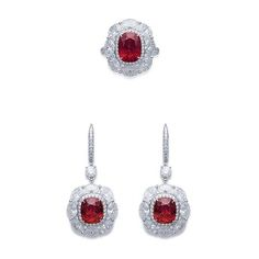 A SET OF RUBY AND DIAMOND JEWELRY COMPRISING OF A RING WITH CUSHION CUT RUBY AND PAVE-SET DIAMONDS AND A PAIR OF EAR PENDANTS EN SUITE.