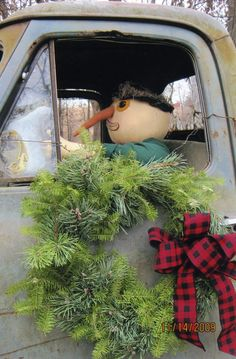 Christmas Decorations .... Mr. Snowman in the drivers seat of an old truck. Also decorated with a wreath on its door