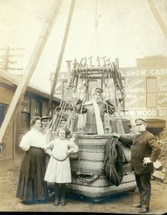 Morris A. Heimann (far right) with his daughter and wife (standing in front) with the balloon basket he planned to use in the first balloon flight by a woman in St. Louis. (1909)