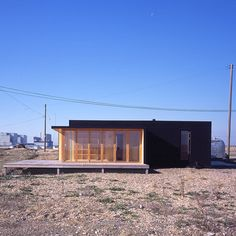 Black Rubber Beach House on Dungeness beach in Kent, England by Simon Conder Associates
