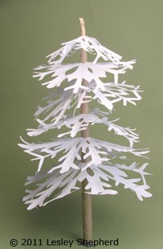 Assembling a miniature winter tree for a village scene from cut paper snowflakes.