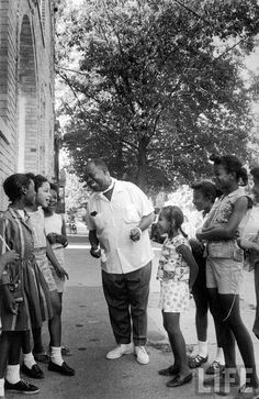 Musician Louis Armstrong with neighborhood kids in Queens. New York, 1965.