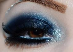 Charcoal grey glittery smokey eye make-up with a line of four crystals along the brow.