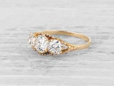 Antique Victorian three stone engagement ring made in 14K yellow gold centered with a GIA certified .60 carat J color SI1 clarity old mine cushion cut diamond accented with two old mine cut diamonds weighing approximately .55 carats total. Circa 1890