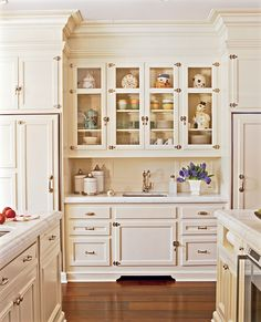 """Serena's collection of vintage cookie jars inspired the kitchen's """"classic, timeless style."""" The jars are showcased in glass-front cabinets with hefty polished nickel hinges and pulls. Adding to the vintage look are a separate refrigerator and freezer that are finished with cabinet faces and nickel hardware to resemble old-fashioned iceboxes."""
