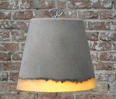 Le concepteur hollandais Renate Vos tisse des matières diversent ensemble afin de leur donner vie. La lampe Concrete fusionne le caoutchouc de silicone et le béton. Le point de rencontre entre ces deux élément, procure une bande sinueuse, célébrant la fusion du doux et dur, de l'opaque et du translucide.