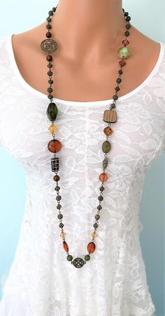 Long chunky beaded necklace handmade by Ralston Originals. This Bohemian style necklace is made with large chunky brown, and green acrylic beads, antique gold metal beads, antique gold filigree beads, and antique gold brass filigree round connectors. The use of acrylic beads makes