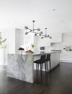 Modern Kitchen Design Modern white kitchen is illuminated by gray glass modular pendant lights fixed over a white center island seating sleek black stools at a gray marble waterfall countertop. Modern Kitchen Island, Kitchen Island With Seating, Modern Kitchen Design, New Kitchen, Kitchen Dining, Kitchen White, Kitchen Islands, Kitchen Layout, Marble Island Kitchen