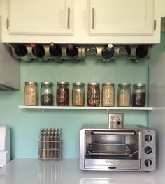 Our space-saving solution in our little galley kitchen. Instead of mounting Ikea wine racks to a wall vertically, we mounted them to the underside of our kitchen cabinet. Two fit perfectly. Also, we added the narrow little shelf and used simple Ball canning jars to contain rice, trail mix, etc.  P.S. - you can write labels on glass jars using a Sharpie and remove later with dish soap.