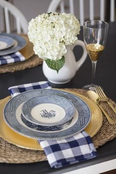 blue and white tablescape with antique Currier and Ives, gold wine glasses, gold flatware