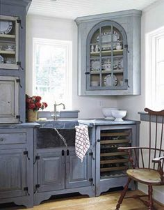 The upper cupboard to the left of the sink acts as an appliance garage and sits right on the soapstone counter, which makes it easy to clean up spills from the coffeemaker inside. To the right is a Sub-Zero 424 wine refrigerator. Reproduction Windsor chair from Bryce M. Ritter Furniture.   - HouseBeautiful.com