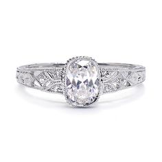 This vintage-inspired engagement ring features an oval shaped center mounting with pave diamonds, milgrain, engraving, and artistic cutout details for an incredibly unique look.