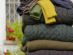 Pile of fall-colored sweaters - 10 Free Sweater Knitting Patterns