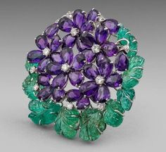 CARTIER An Art Deco 1950s Brooch - Amethyst Diamonds, Emeralds and Amethysts Signed Cartier, London .Diameter: 6cm, 2.3in.