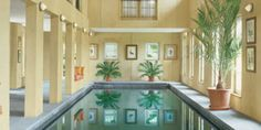 In her pool house, jewelry designer Elizabeth Locke's gem of a lap pool. Weru windows. Banquette cushions in Brunschwig & Fils woven; pillows in Jim Thompson silk. Prisma Architectural Lighting fixtures. Waterworks limestone flooring. I normally don't like indoor pools, but this one is so elegant!