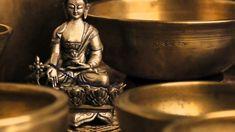 Tibetische Klangschalen rund um eine Buddha Statue