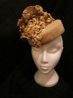 Vintage felt was reblocked, stiffened into pill box, brim was shaped into a fan for the top & sculpted side of the hat. Roses are shades of gold, cream and coffee fabrics. Roses cascade down to the front from dark to light. The pearls were scattered over the hat . Back of hat has two large roses next to fan shape and the edge of the hat was finished with the darker fabric, lined in cream.