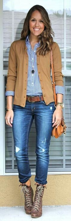 Tan cardigan over blue checked shirt with blue jeans.