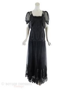 From the 1930s, a jet black lace gownwithattached faux bolero bodice, puffed sleeves, and flowing skirt. Matching slip with net lace at bodice and scalloped h