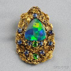 Arts & Crafts Black Opal, Demantoid Garnet, and Sapphire Brooch, Tiffany & Co., designed as a pear-shape black opal with demantoid garnets and sapphires among gold grapevines, lg. 1 5/8 in., signed