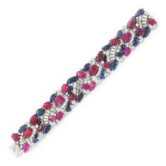 An Art Deco Sapphire, Ruby and Diamond Bracelet Designed as an openwork panel, set with carved rubies and sapphires, spaced by baguette and circular-cut diamonds, mounted in platinum, circa 1930.