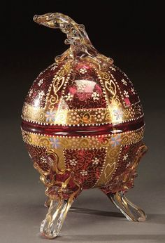 A MOSER RIGAREE FOOTED ENAMELED BOX; circa 1890; egg form in cranberry glass decorated gilt panels and scrolling adorned with white and blue daisies. Height 6.5 inches.